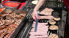 Minced meat cutlets and sausages fried on grill on street food festival Bulgaria Stock Footage