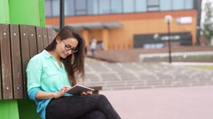 Elegant young girl using the mini-tablet Stock Footage