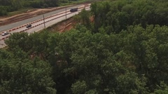 Drone flying from trees and showing how crane laying pipes for road construction Stock Footage