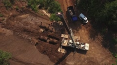 Aerial view of laying pipes by crane, workers dressed in white and orange Stock Footage