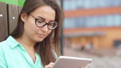 Beautiful student in glasses with a digital mini tablet Stock Footage