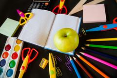 School supplies and a large green apple on  notepad in the center Stock Photos