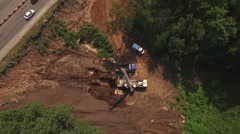 Drone flying down,workers shipping pipes in truck with blue cabin by crane in Stock Footage