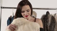 Elegant woman choosing fur jacket in front of clothing rack with fur coats Stock Footage