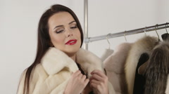 Smiling woman in fur jacket in front of clothing rack with fur coats Stock Footage