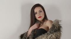 Attractive woman in fur coat and bodycon dress posing on white background Stock Footage