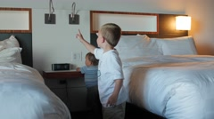 Boys play with the light switches in a hotel room Stock Footage