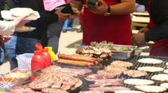 People buy meat dishes grilled on big street food festival in Sofia Bulgaria  Stock Footage