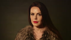 Beautiful woman in lingerie and fur jacket posing on dark background Stock Footage
