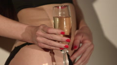 Body of a woman in sexy lingerie with glass of champagne in hand Stock Footage