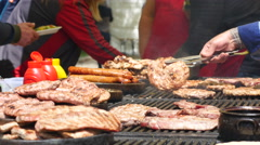 Cooking meat dishes on a grill on big street food festival in Sofia Bulgaria  Stock Footage