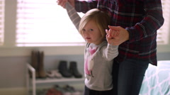 A little girl walking on her mother's feet while holding her hands Stock Footage