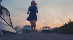 Young girl in blue dress run on wooden pier at coast on sunset. White yachts Stock Footage