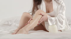 Young woman in white satin robe applying cream on her legs sitting on the bed Stock Footage