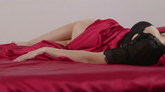Young woman in sexy black lingerie lying on red linen in bed Stock Footage