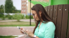 Elegant young girl using the mini-tablet. Beautiful student in glasses Stock Footage