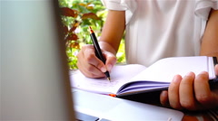 Slow motion on woman hand writing on notebook in the coffee shop Stock Footage