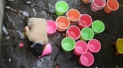 A Chinese female sanitation workers are washing the plastic bucket Stock Footage