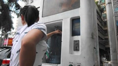 A woman is buying water from an automatic water vending machine Stock Footage