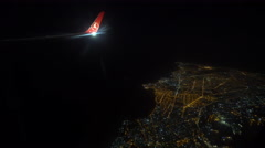 Illuminated city at night and wing of airplane - view from plane Stock Footage