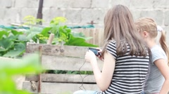 Two girls playing cell phone on nature Stock Footage