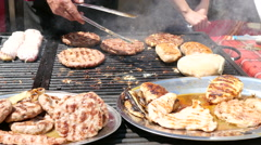 Cooking meat dishes on a big grill table on street food festival Balkan cuisine Stock Footage