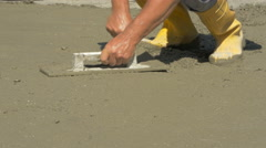 Leveling concreted floor with spatula and trowel,hands close up by Sheyno. Stock Footage