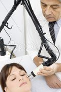Young caucasian woman receiving electrostimulation lifting from a male doctor Stock Photos