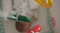 Extreme close up of a swinging mobile toy over the unfocused sleeping baby Stock Footage