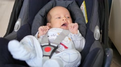 Cute little infant yawning in a baby car seat Stock Footage
