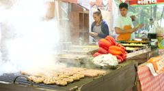 Cooking meat cutlets and sausages fried on grill on street food festival Stock Footage