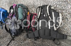 Backpacks near an airport wall ready to leave Stock Photos