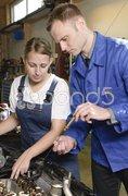 Azubi und Meister in Autowerkstatt Stock Photos