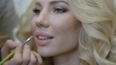 Make-up artist doing make-up for model Stock Footage