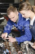 Azubi und Meister in Autowerkstatt Stock Photos
