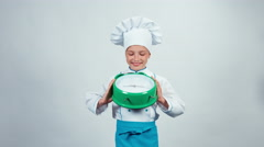 Happy chef cook child 7-8 years holding alarm clock and standing isolated Stock Footage