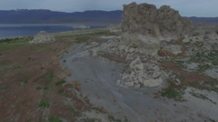 Flying Past Weird Desert Rocks Towards Lake and Mountains Stock Footage
