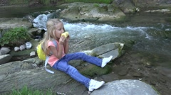 4K Girl Eating Apple by River, Child Relaxing at Camping on Mountains Trail Stock Footage