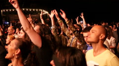 Cheering crowd spectators enjoy a music concert clapping by a stage Stock Footage