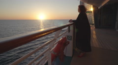 Woman passenger stands on cruise ship deck at sunset - midnight sun Stock Footage