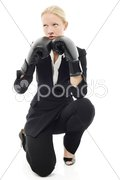 Portrait of a young caucasian businesswoman with aggressive air and boxing glove Stock Photos