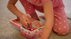 Little girl in her pajamas putting her jewelry in her jewelry box Stock Footage