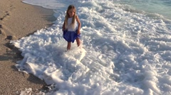 4K Girl Playing on Beach at Sunset, Happy Child Walking in Sea Waves on Seaside Stock Footage