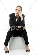 Young businesswoman sitting on a briefcase on white background studio Stock Photos