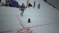 Snowboarders without one shoe jump for second on slope in snowy mountain. Smile Stock Footage