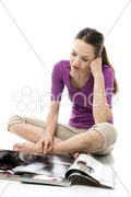 Young woman sitting on the floor reading a magazine on white background studio Stock Photos