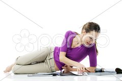 Young woman lying on the floor reading a magazine on white background studio Stock Photos