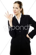 Young businesswoman with her hand indicating ok on white background studio Stock Photos