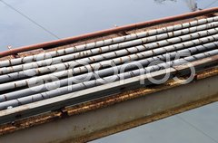 Rusty pipeline over a river in Indonesia Stock Photos