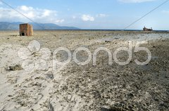 Low tide in shoreline with a cabin and an aground boat Stock Photos